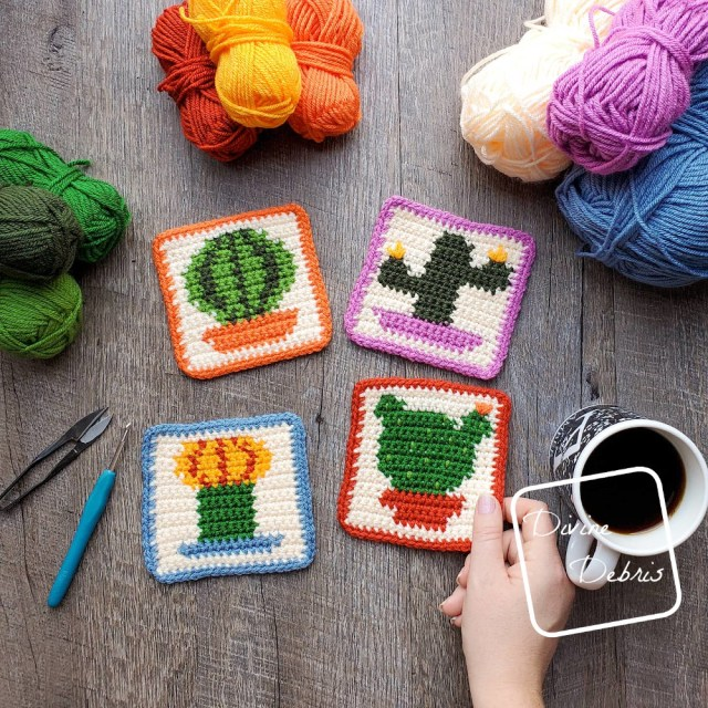 [Image description]The four cactus coasters lay in the center of the photo, with stacks of 3 skeins of yarn around the top of the photo and a white woman's hand holding the bottom right-hand coaster.