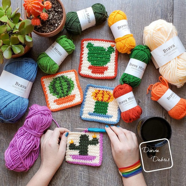 The four cactus coasters lay in the center of the photo, with skeins of yarn around the top of the photo and a white woman's hands finishing the bottom most coaster.