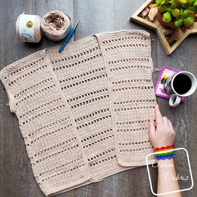 [image description] the tan colored Kieran cardigan rochet pattern lays in the center of the photo on a wood grain background, a white woman's hand holds the bottom right corner, a cup of coffee is off to the right and 2 skeins of yarn are on top.