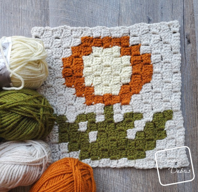 [Image description] the C2C Mum Afghan Square lays flat on a wood-grain background with 4 skeins of yarn laying on the left side and bottom corner of the square.