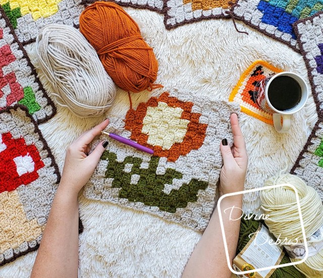[Image description] A white woman's hands hold a partially finished C2C Mum Afghan square in the center of the photo. 4 skeins of yarn, a cup of coffee, and peeks of the previous C2C Plant squares can be seen along the edges of the photo.