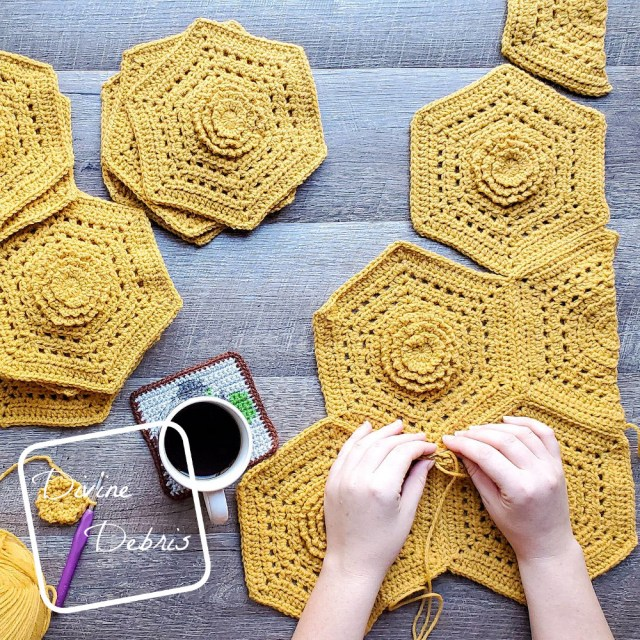 [Image description] A top down view of two white woman's hands seaming together the mustard colored hexagons from the Florence Hexagon Blanket. A cup of coffee sits to the middle left of the hands and a pile of hexagons sits to the left top of the photo
