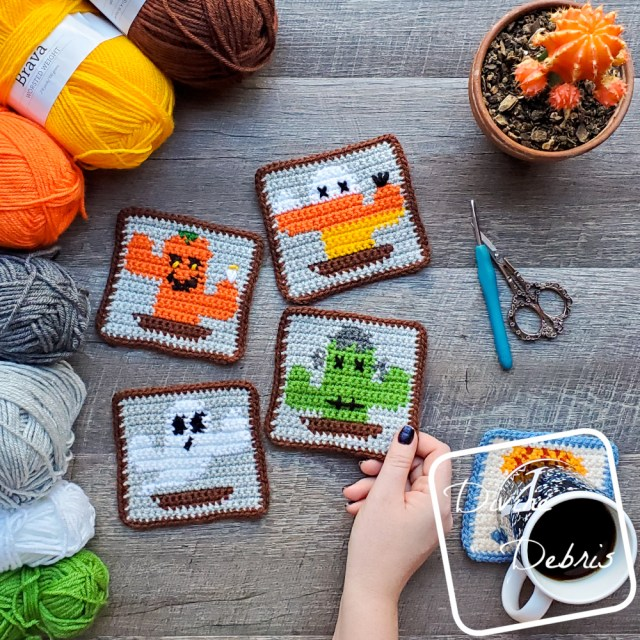 [Image description] The four Halloween Cactus Coasters sit in the center of the photo on a wood grain background, with 7 skeins of yarn on the left, a cup of coffee on the bottom right, scissors an a crochet hook on the middle right, and a cactus plant on the top right. A white woman's hand holds the corner of the bottom right Frankencactus coaster.