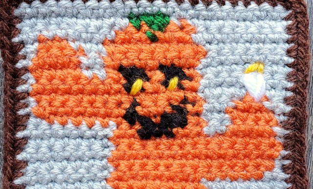 [Image description] Close up of the Cactus-O-Lantern's eye details and flower.