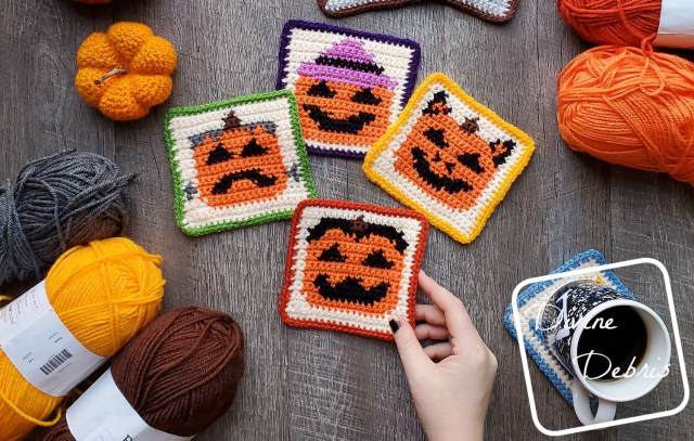[Image description] Halloween Pumpkin Coasters crochet patterns laying flat on a wood-grain background, a white woman's hand holds the bottom coaster and 3 skeins of yarn are on the bottom left and 2 skeins are on the top right.