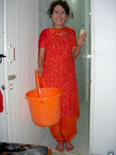 Divine Light Vibrations, Glenn Younger author and spiritual coach in India bathing in a bucket