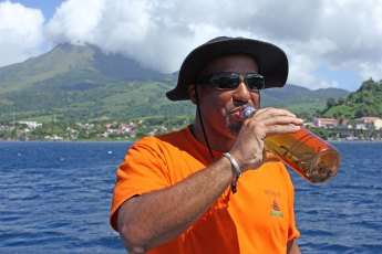 Steve Bennett (Uncommon Caribbean) enjoys a swig of planteur, a local favourite often served by the captain after the last dive of the day. Photo © Jeffrey Gallant | Diving Almanac