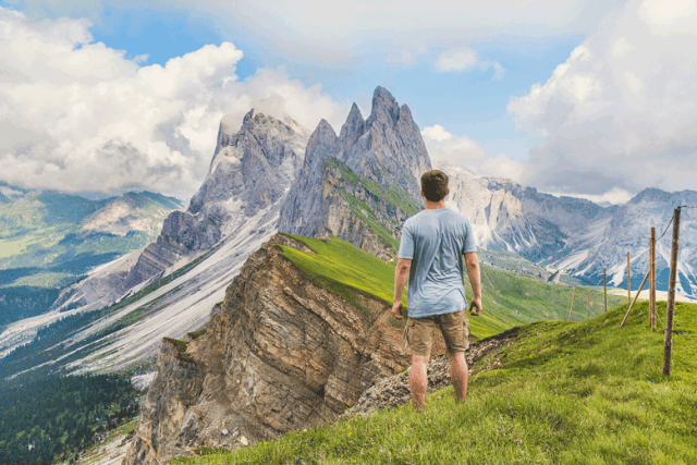 man standing on a mountain, staring off to a mountain