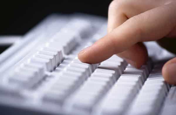 Mão digitando no teclado do computador era da informação