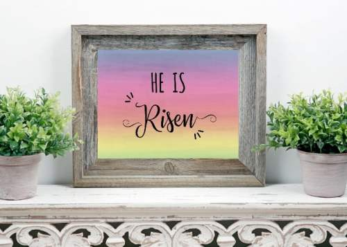 He is Risen Free Easter Printable shown in a rustic wood frame