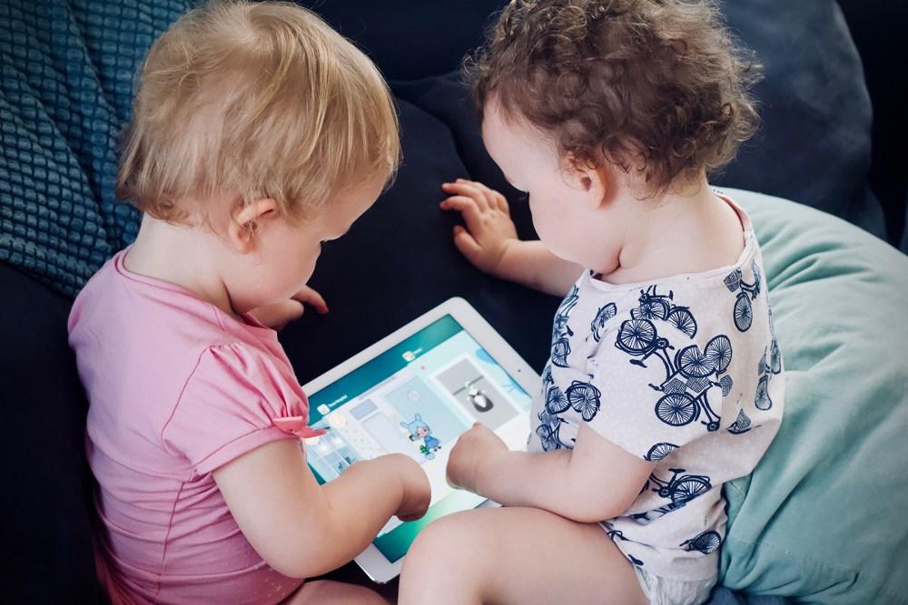 Dos infants juguen amb una tauleta al sofà.