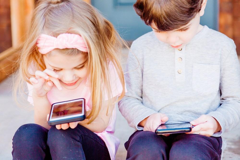 Una nena i un nen juguen amb els seus respectius telèfons intel·ligents.