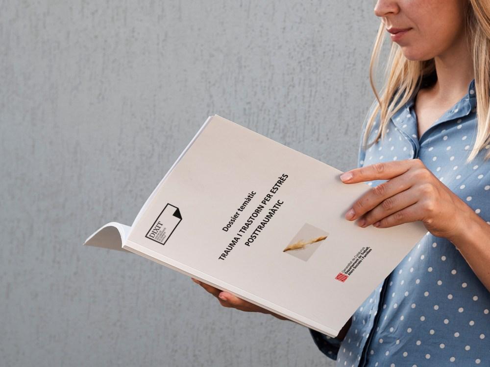 Una dona llegeix el dossier sobre trauma i estrès posttraumàtic