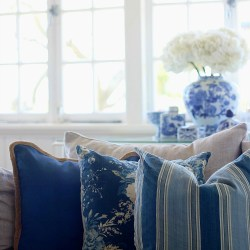 blue cushions with linen sofa. Mixing patterns together - plain, geometric, and floral.