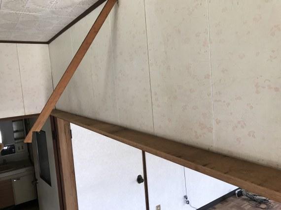 吊り下げられている棚をバールで一部撤去した後