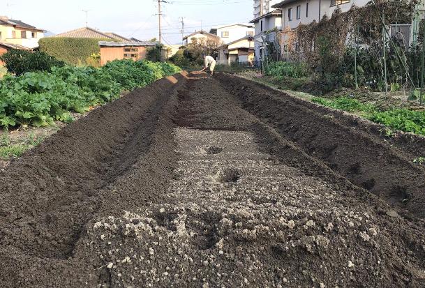 反対側も寄せた土をクワでならす