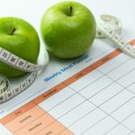 60677206 – weekly meal planner with green apples and tape measurement