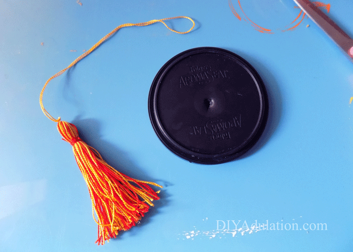 Lid with a hole in the center next to red and yellow tassel