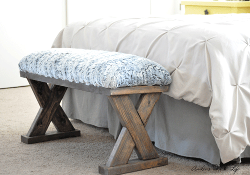 Wooden x-bench with upholstered seat at the foot of a bed