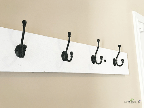 White wooden board mounted on a wall with black coat hooks on it