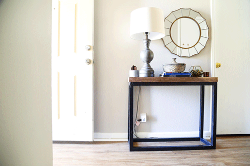 Styled wooden and metal entry table next to an open door