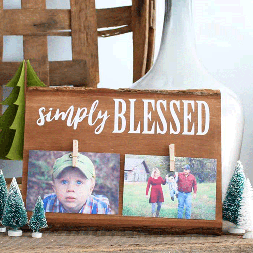 Wooden plank with 2 photos clipped at the bottom and the words Simply Blessed at the top