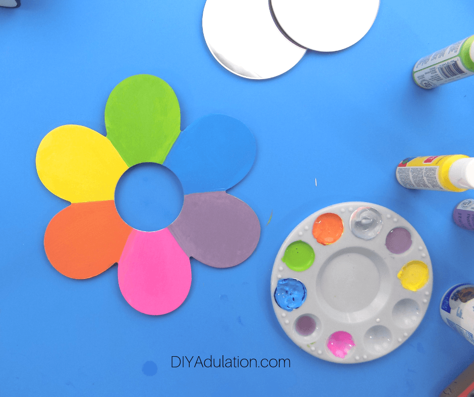 Wooden Flower with Rainbow Painted Petals next to Paint Pallet