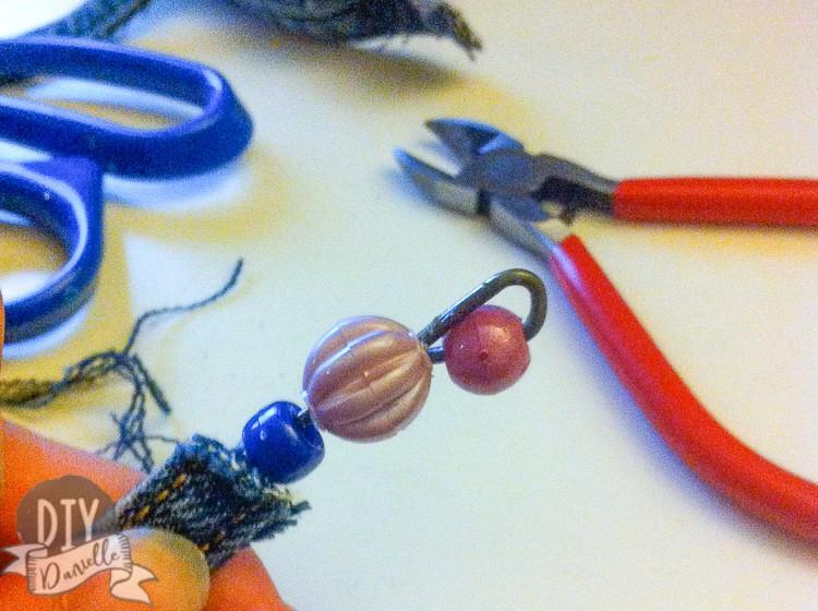 Beads on the end of a DIY denim bracelet.