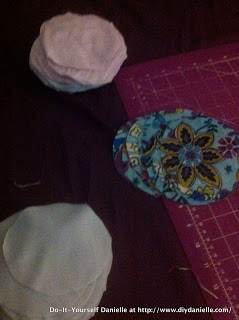Cutting fabric to make nursing pads.