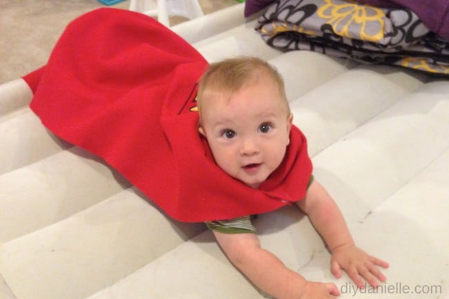 Baby wearing a no sew superhero cape: learn how to make this cape without sewing.