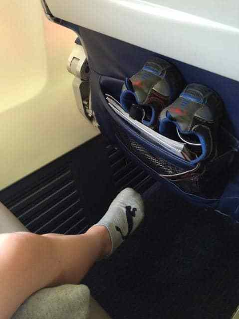 Shoes stored for the flight so the kids can't kick as hard if they bump the seat in front of them.