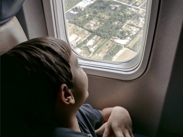 Child watching out the window on an airplane. Traveling with kids can be easy and fun for kids.
