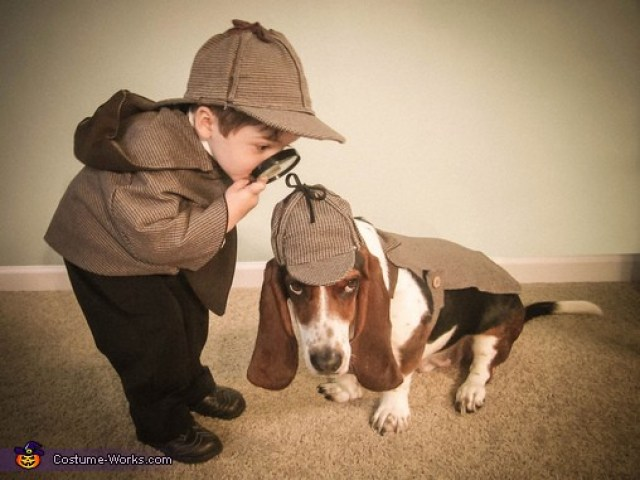 The dog's face is priceless, and they make a dynamic duo in the Holmes and Watson costumes!