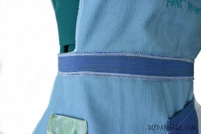 Waist strap sewn onto apron.