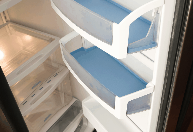 Photo of a clean refrigerator. Get some quick and easy hacks for cleaning the refrigerator.