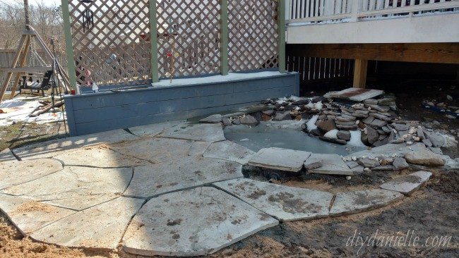 Stone laid for the patio around the pond.