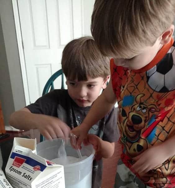 Kids helping make gifts for their teachers, mason jars full of orange mint bath salts.