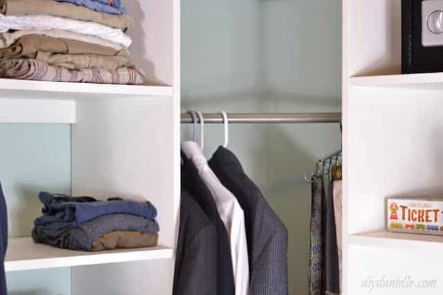 White closet shelves and a silver rod with clothes hanging. Shelves are plywood with veneer covering the raw edge.