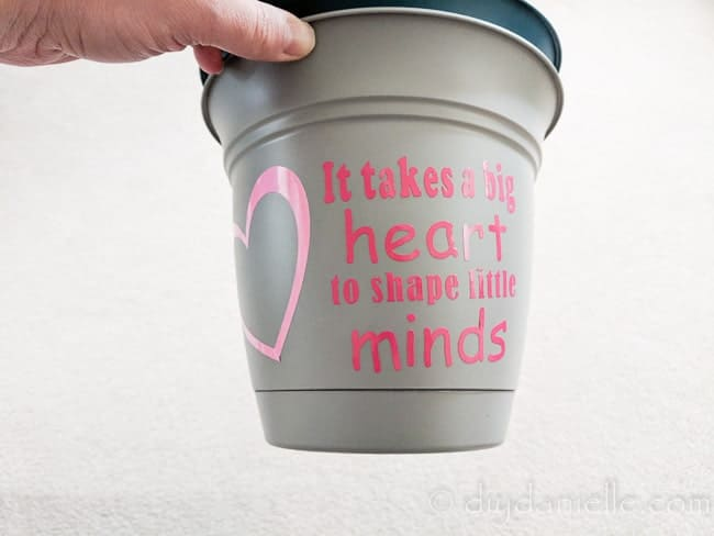 "Pot with a vinyl design that says ""It takes a big heart to shape little minds."""