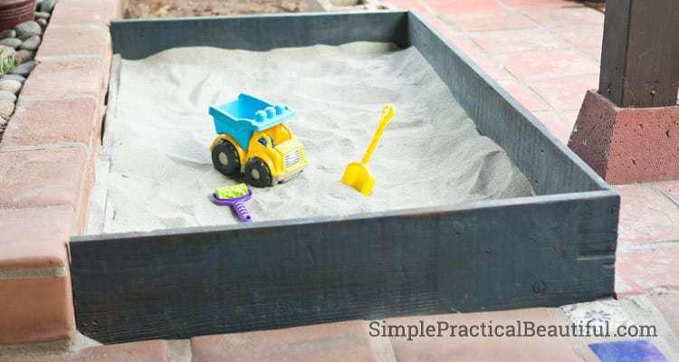 Gray handmade sandbox for an outdoor kids space.