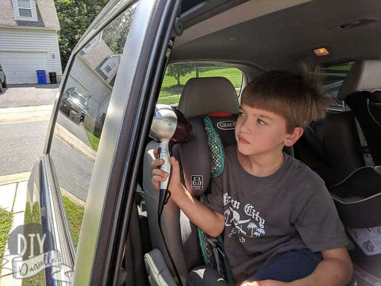 Six year old helping clean stickers off the car windows with a hair dryer.