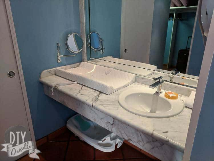 Changing pad by the sink at the hotel. Bath underneath for baby.