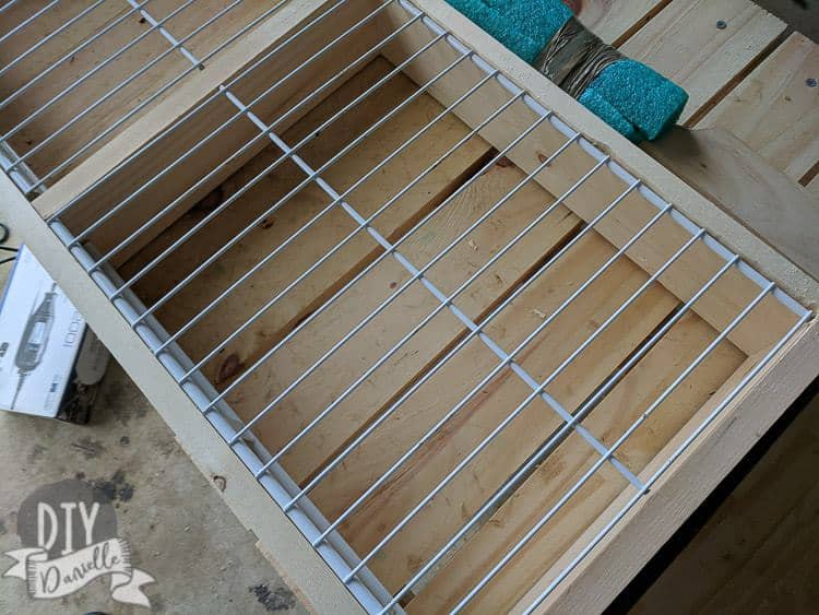 Old wire shelves sitting on a lip in the wood frame. This is to be used as a drying rack.
