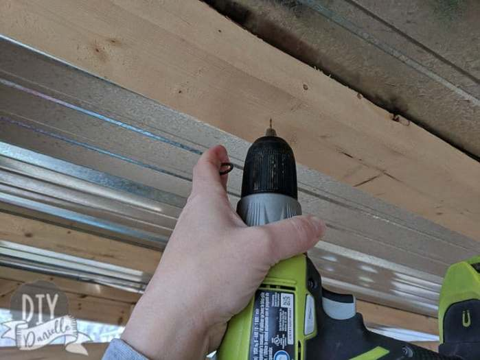 Using my drill to create a small hole that I can screw my hook into. This hook will allow me to hang the light bulb from the ceiling of the shed.