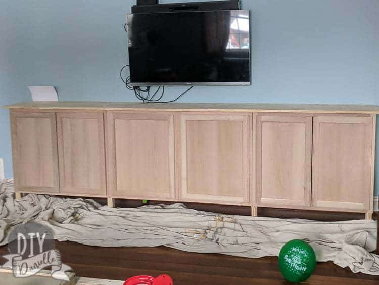 Unfinished wood cabinets installed as entertainment center storage. They'll be finished with stain, then dry brushed.