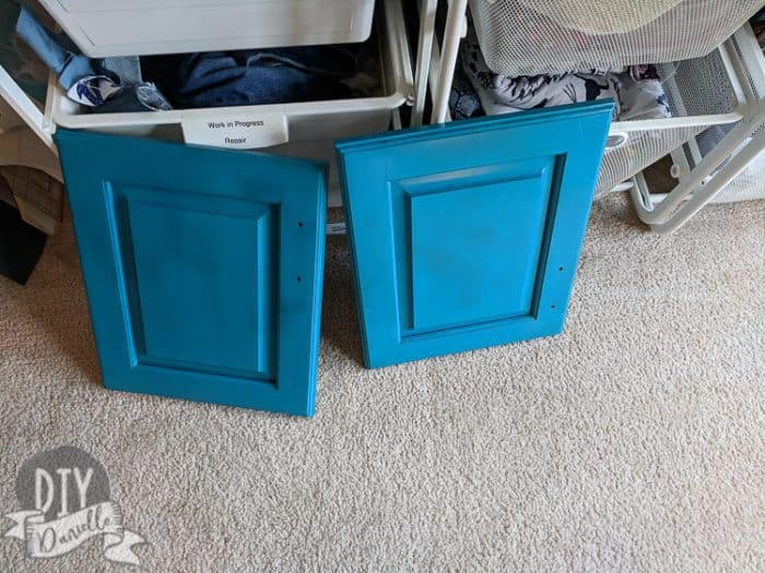 Upcycling a cabinet door. Painted blue before adding vinyl.