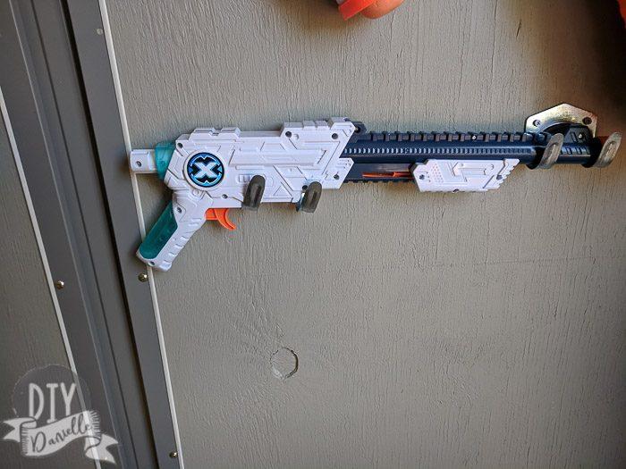 Two hooks holding up a Nerf gun horizontally.