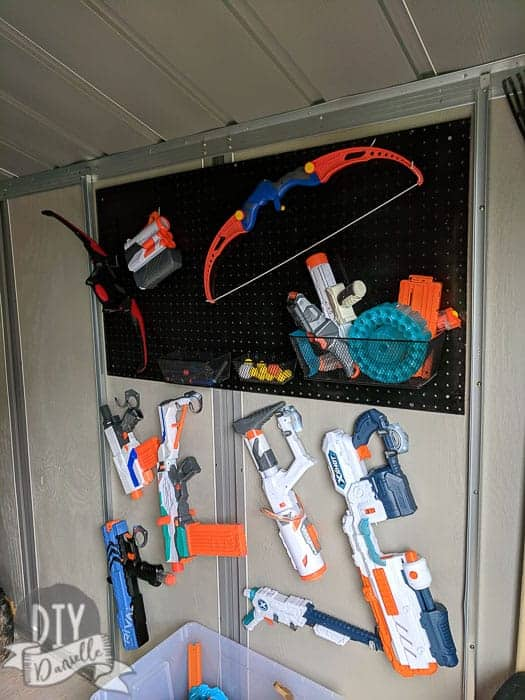 Nerf gun storage in the kids garage. Super organized with cheap $1 hooks, pegboard, and small containers.