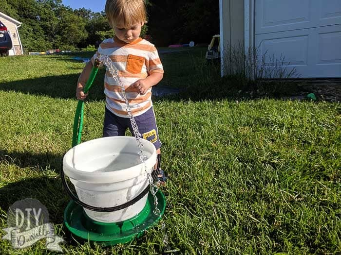 Toddler helping fill a water bucket for the ducklings.