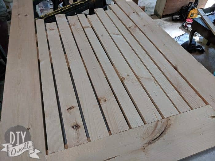 Lining up the vertical pieces of the bottom half of the wood screen door. Note that I drew a little line and put a number for each so I could place them back in the right spot and order.